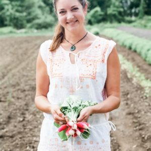 Diana Rodgers holding a bunch of radishes on her farm in Massachusetts.