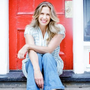 A portrait of Lindsay Cameron Wilson sitting on steps in front of a red door.
