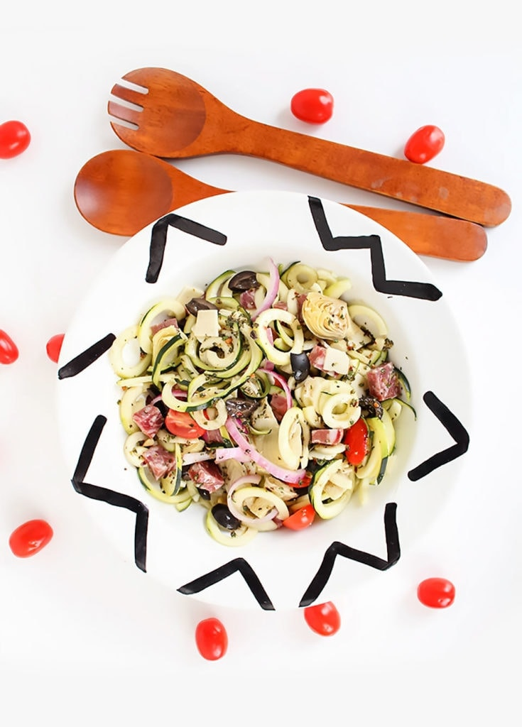 Spiralized Italian pasta salad in a white bowl with tomatoes.