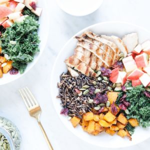 Fall harvest bowl with apples, squash, chicken, kale, and wild rice in two white bowls.