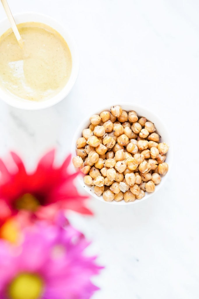 Crunchy chickpeas in a white bowl with white background and flowers.