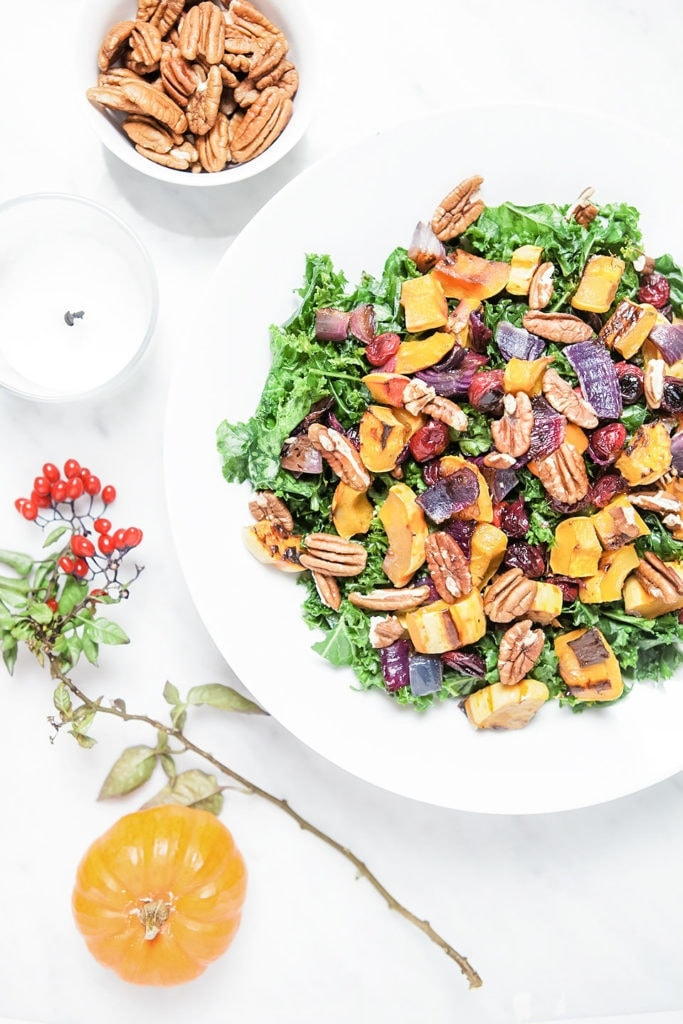 Delicata squash and cranberry kale salad in a white bowl set on a Thanksgiving table.