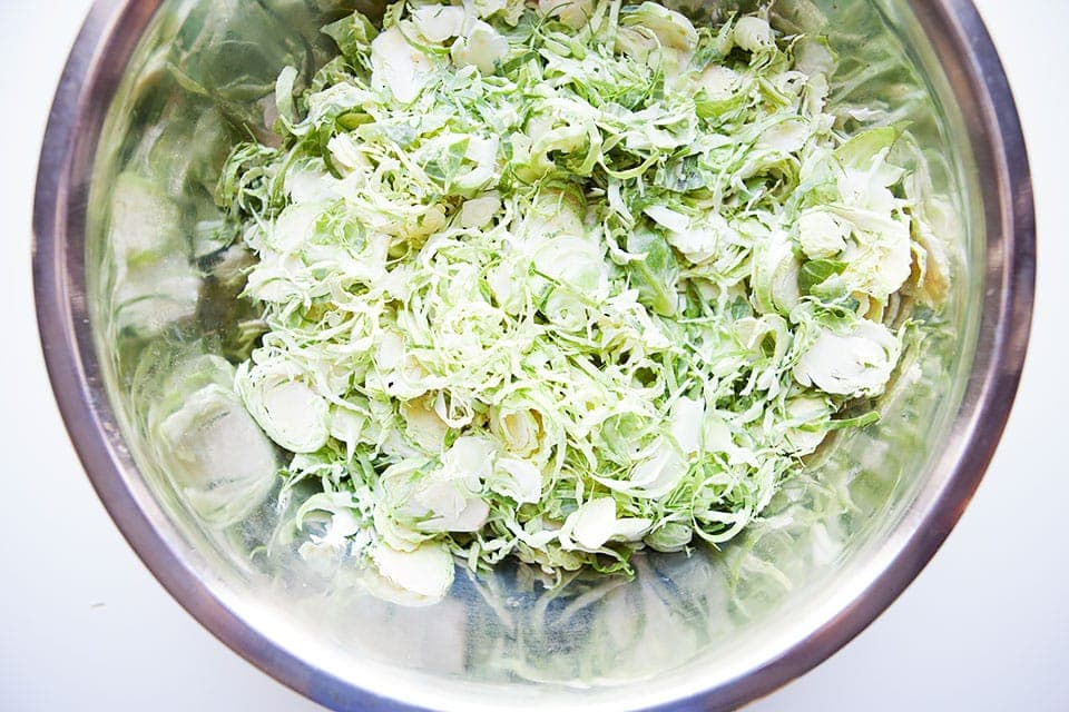 Sliced brussels sprouts in a big metal bowl.