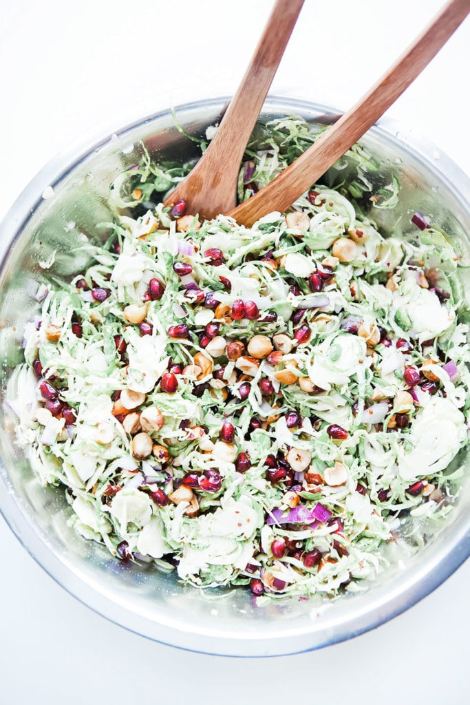 Brussels sprouts salad with pomegranates and hazelnuts in a big metal bowl.