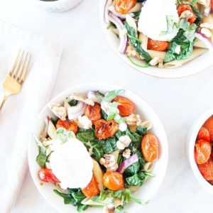 Roasted tomato spinach pasta bowls in white bowl on white background.