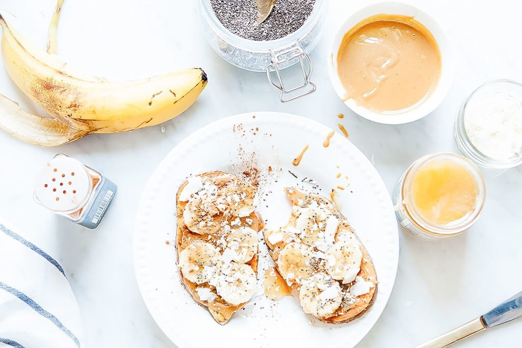 Sweet potato toast on a white plate with peanut butter and slices banana.