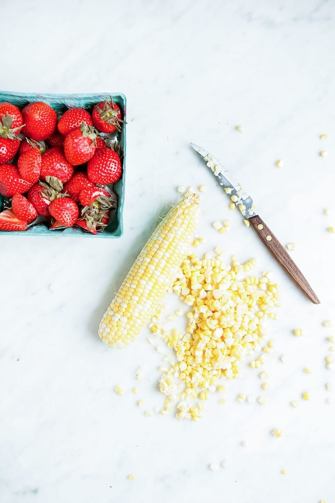 Strawberries and fresh corn and corn kernels with knife on a white background.
