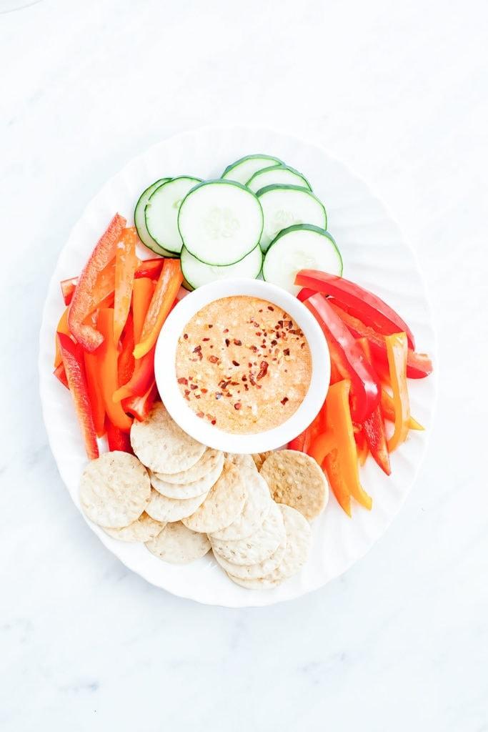 Harissa feta dip on a white platter with sliced vegetables.