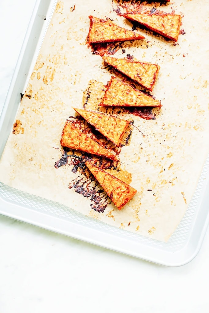 Barbecue tempeh triangles on a baking sheet.