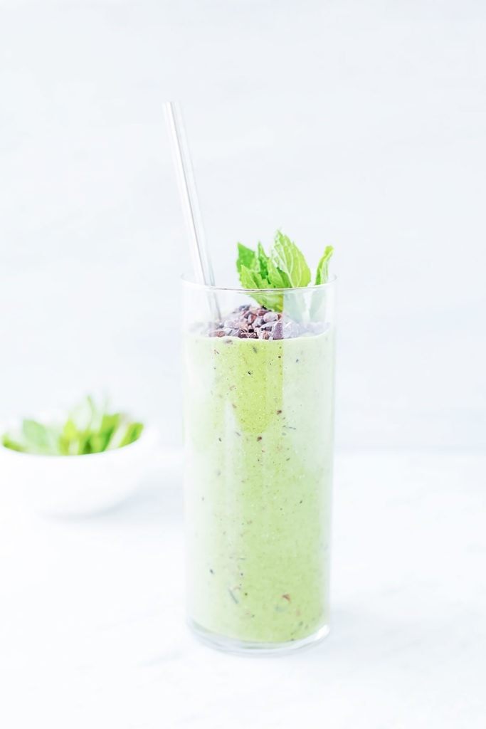 Mint chocolate chip smoothie in a glass with a straw.