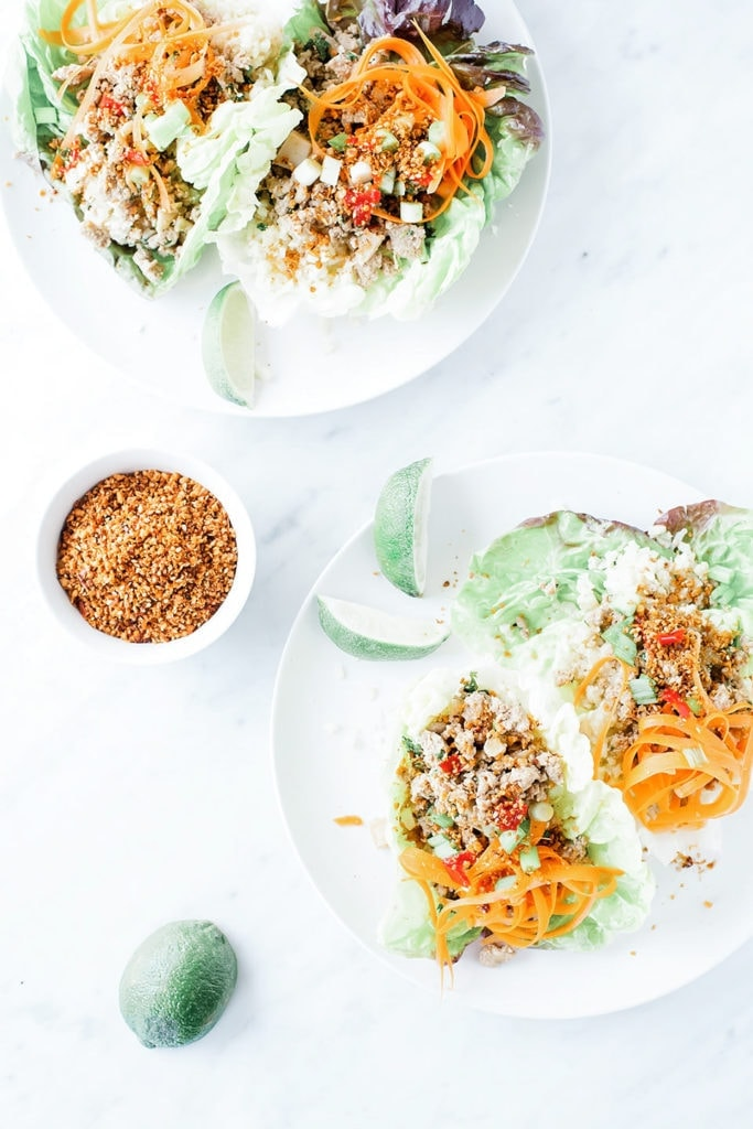 Chicken lettuce wraps with cauliflower rice on white plates with lime slices.