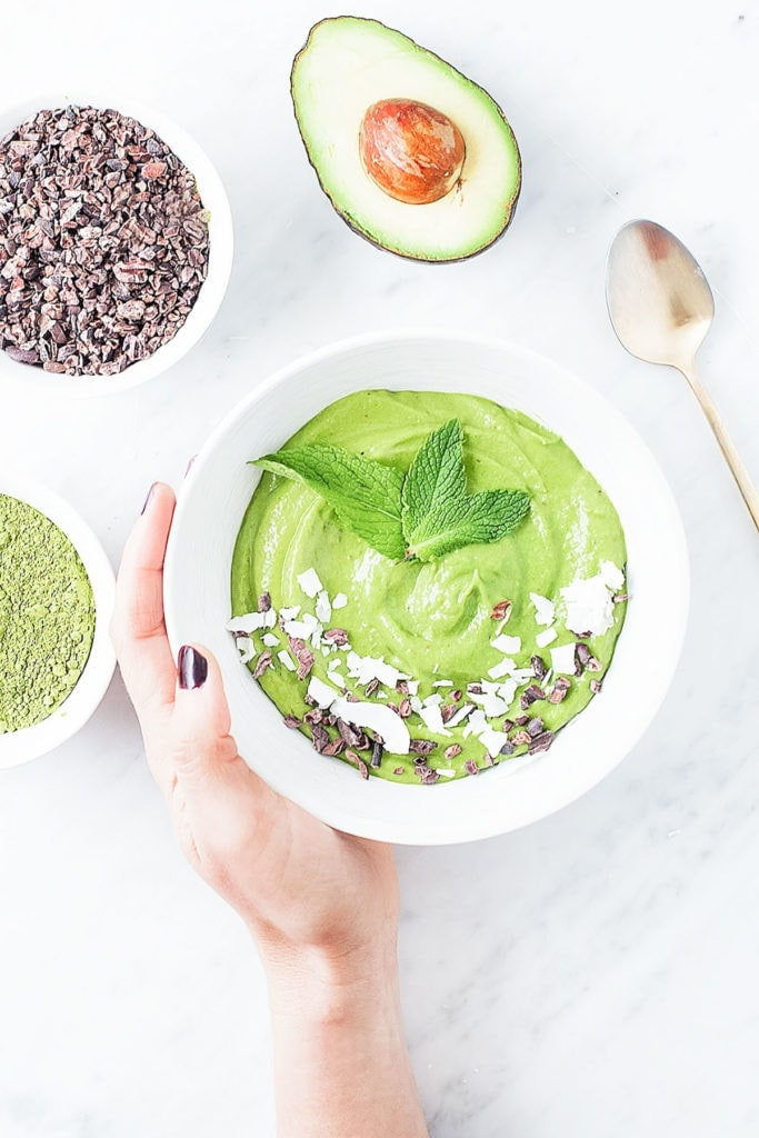 Matcha mint chocolate chip smoothie bowl in a white bowl with a hand holding it and mint leaves on top.