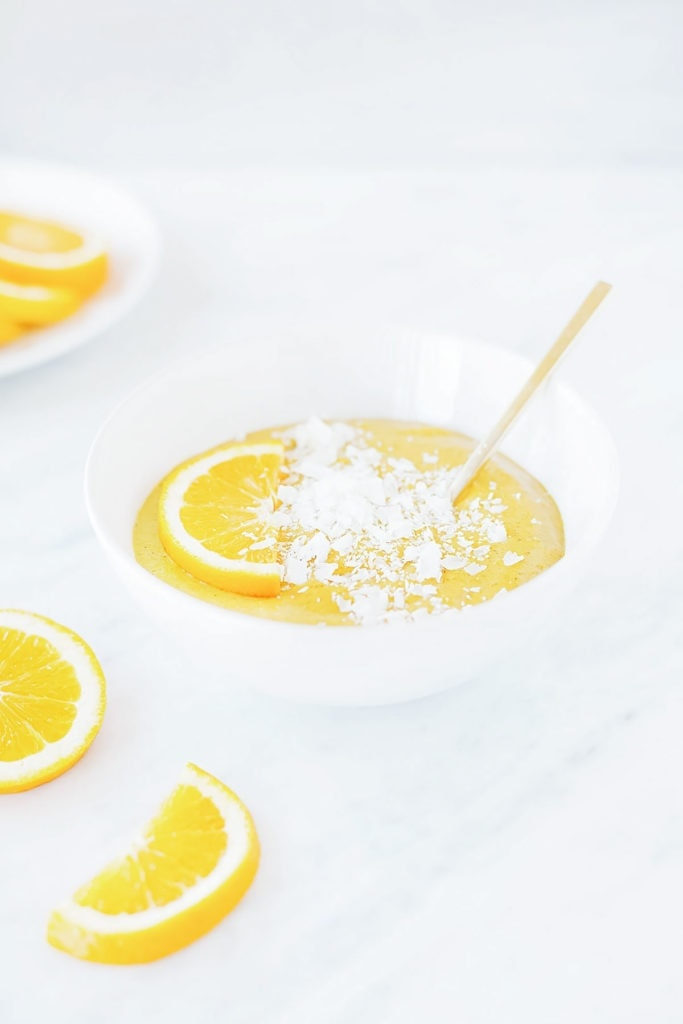 Orange creamsicle smoothie bowl in white bowl with orange slice.