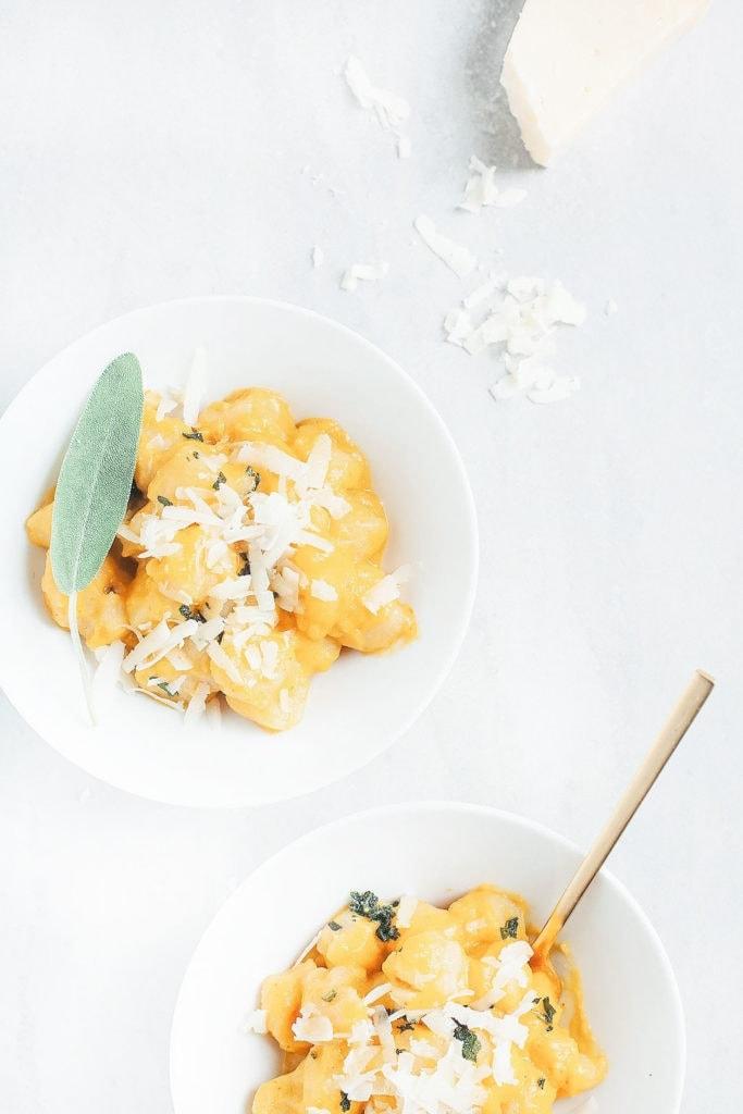 Cauliflower gnocchi with butternut squash sauce in white bowls.