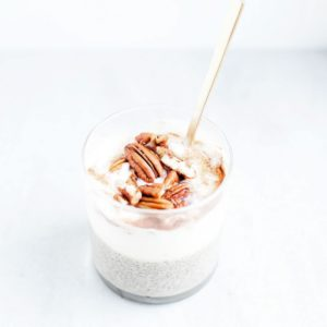 Pecan pie chia pudding in a glass jar layered with yogurt and pecans.