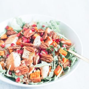 Holiday glow bowls with ginger-tahini dressing in a white bowl with a fork.