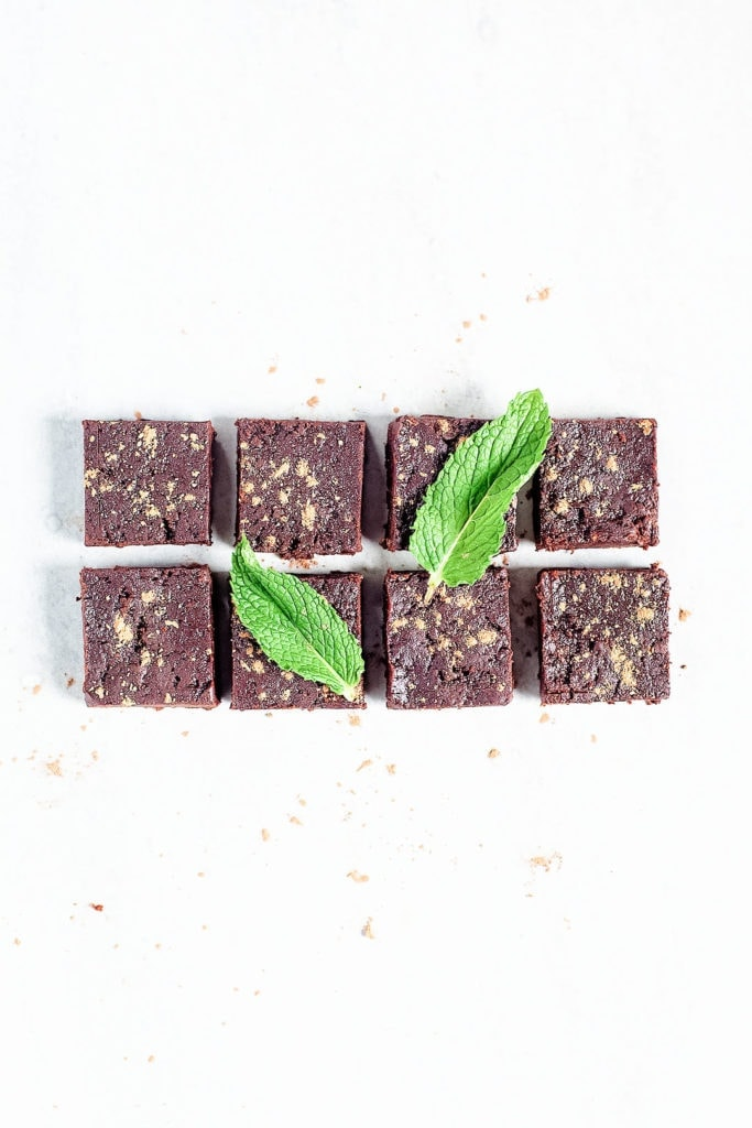 No-bake peppermint brownie bars on white background with mint leaves.