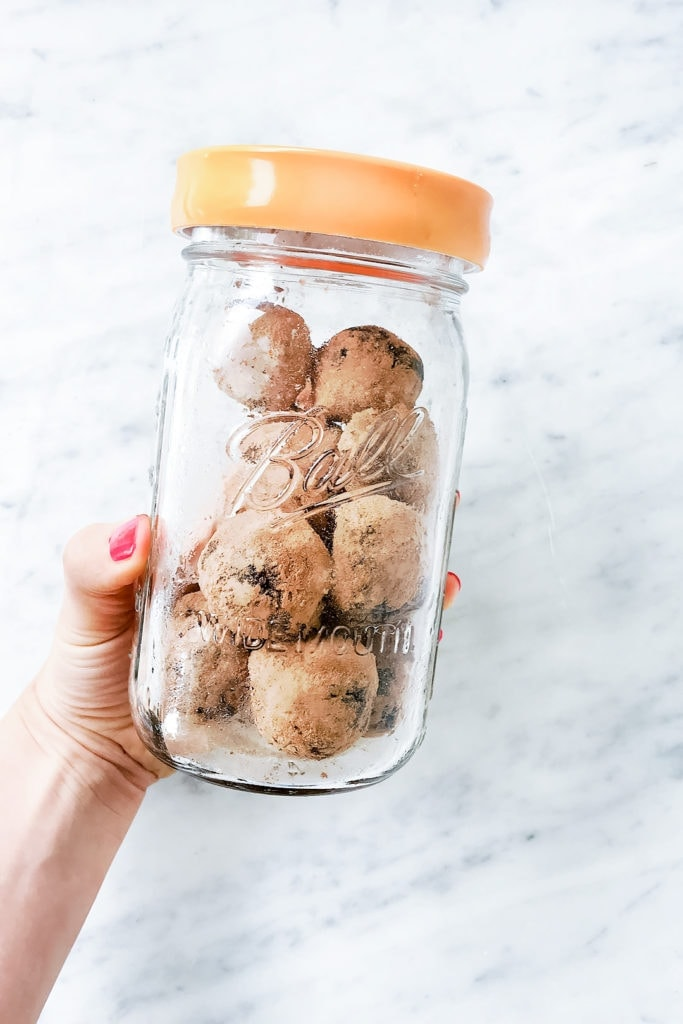 Seed cycling brownie bites in a glass jar being held.