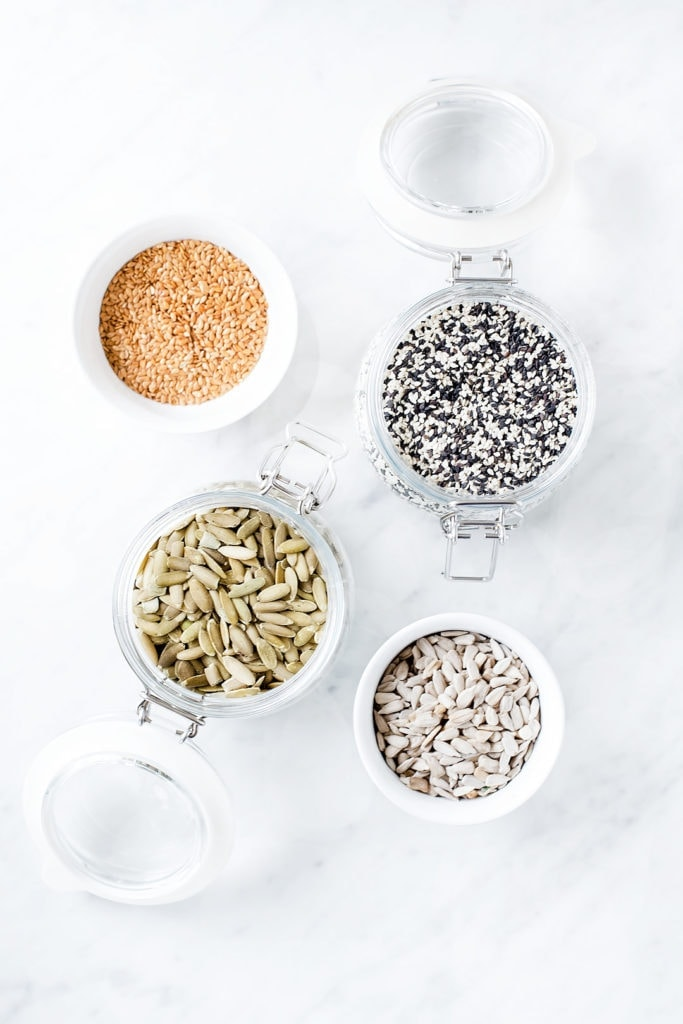 Seeds in jars on a white background for seed cycling.