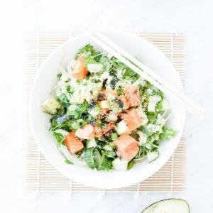Salmon poke bowl in a white bowl with chopsticks.