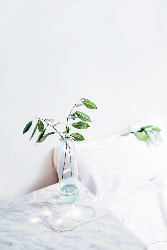 Vase of leaves by a bed.