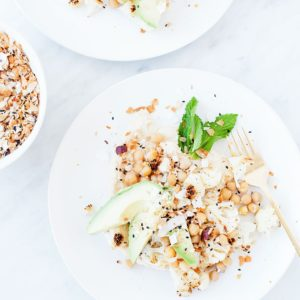 Roasted cauliflower salad with hummus on a white plate.