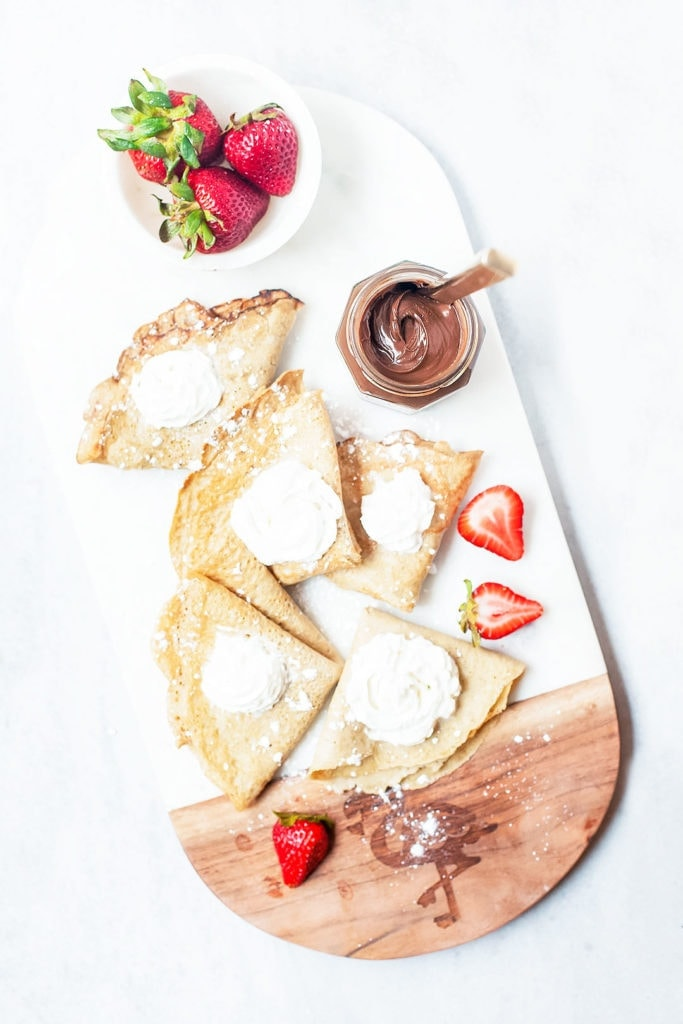 Gluten-free crepes with coconut whipped cream, strawberries, and nutella on a white platter.