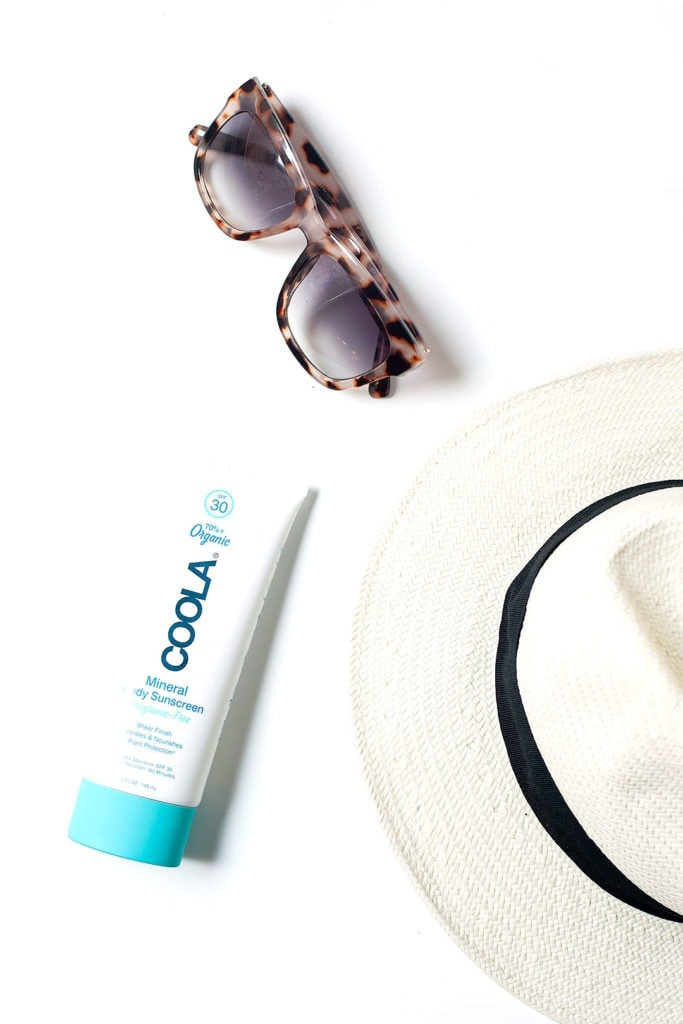 Non-toxic sunscreen with sunglasses and a hat on a white background.