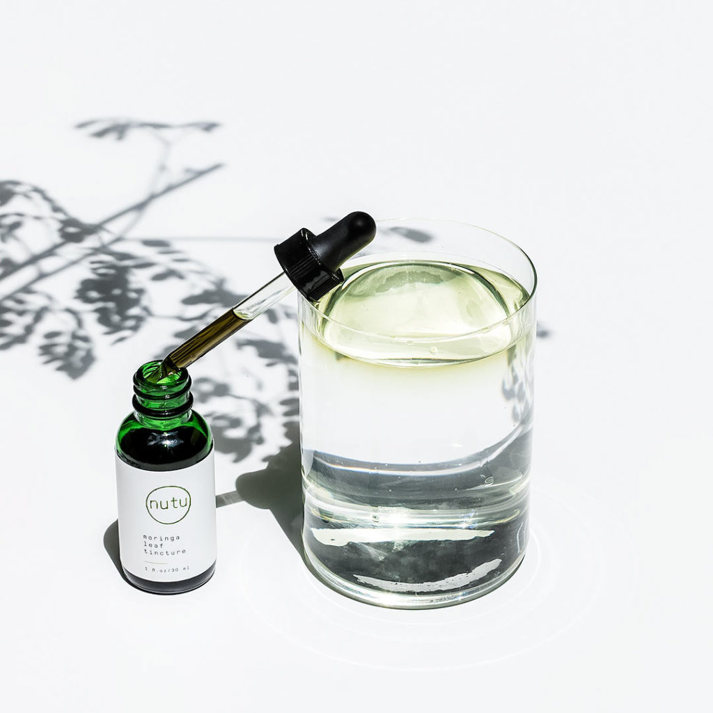 Glass of water with moringa tincture.