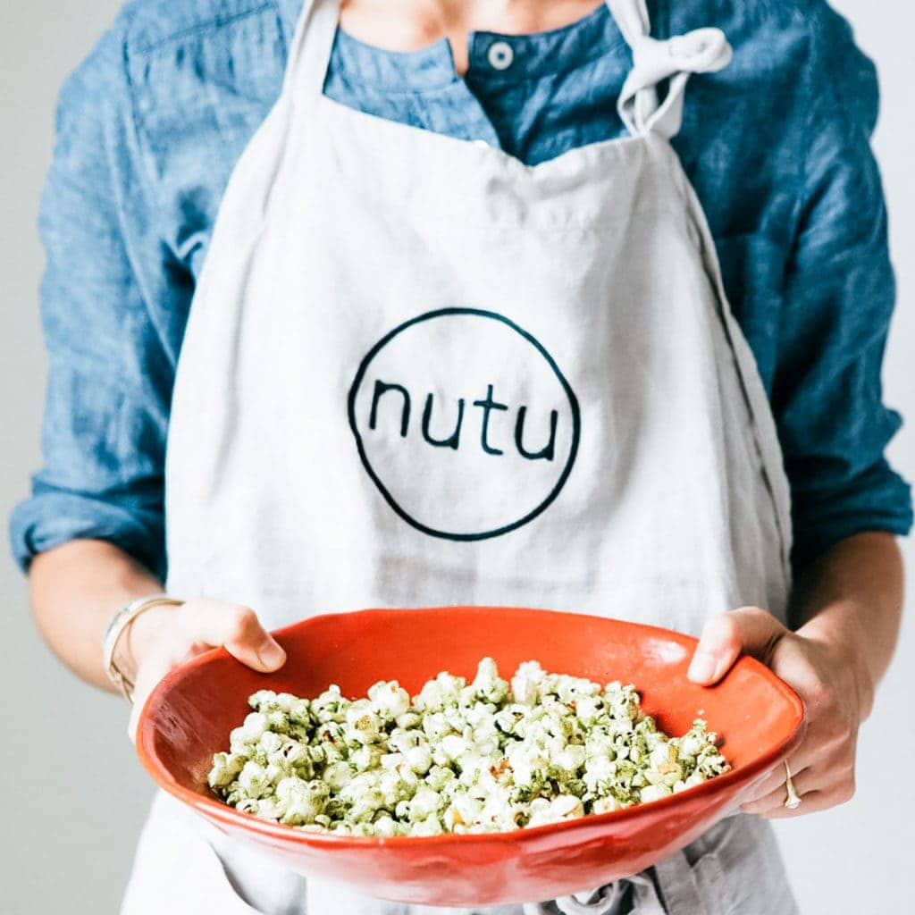 Woman in a apron holding a bowl of popcorn dusted with moringa powder.