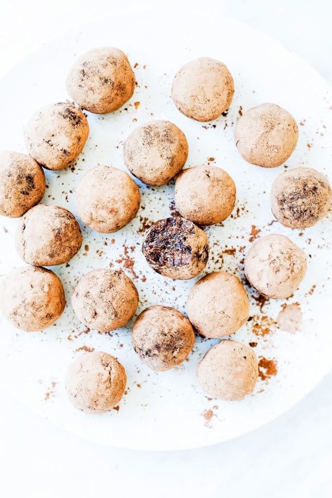 Chocolate collagen energy bites on a white plate.