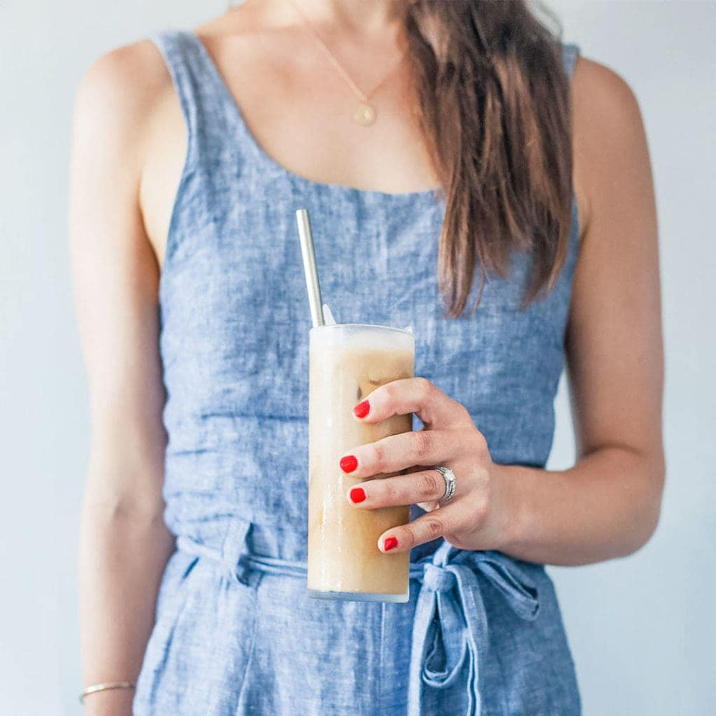 Woman holding coconut cold brew coffee in a tall glass with a straw.