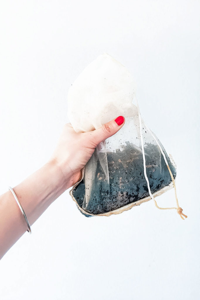 Nut milk bag with coconut cold brew coffee grounds being held by a hand.