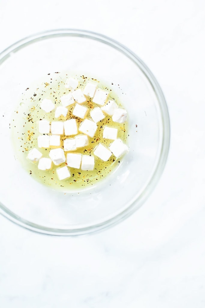 Feta and olive oil in a glass bowl with a white background.