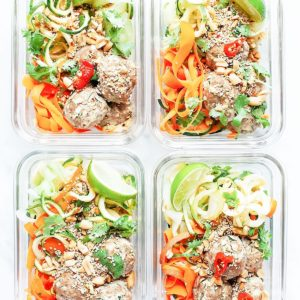 Bánh mì bowls with zucchini noodles, baked turkey zucchini meatballs, and cilantro pesto dressing in meal prep containers.