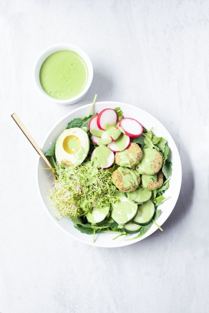 Baked falafel on a salad with green tahini sauce.