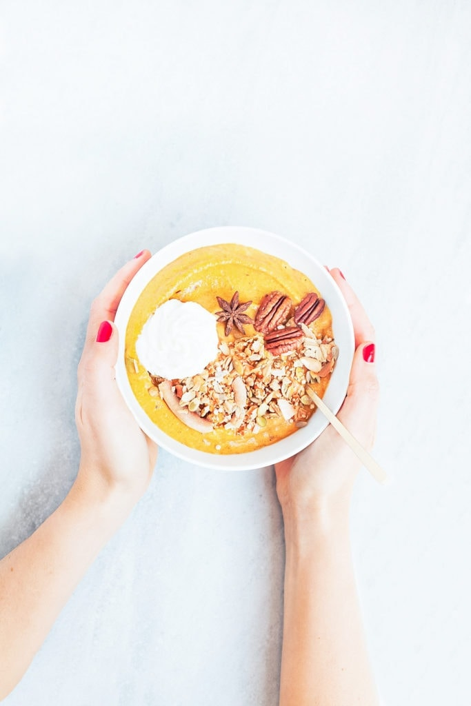 Hands holding a pumpkin pie smoothie bowl.