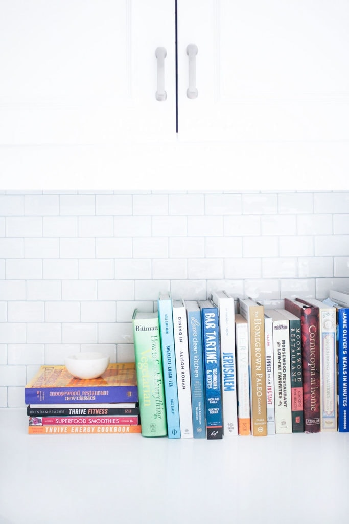 Cookbooks against a white subway tile background in a kitchen.