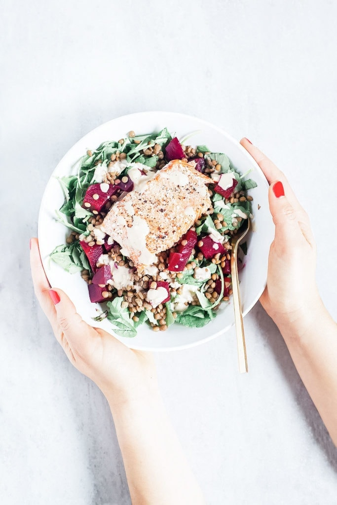 Hands holding a white bowl with a salmon and beet salad.