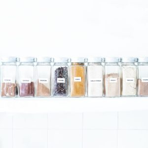 Organized spices lined up on a shelf.