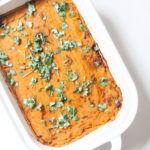 Moroccan shepherd's pie with sweet potato in a white casserole dish.
