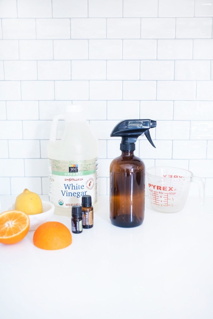 A spray bottle of non-toxic kitchen cleaner with essential oils, an orange, a lemon, and distilled vinegar.