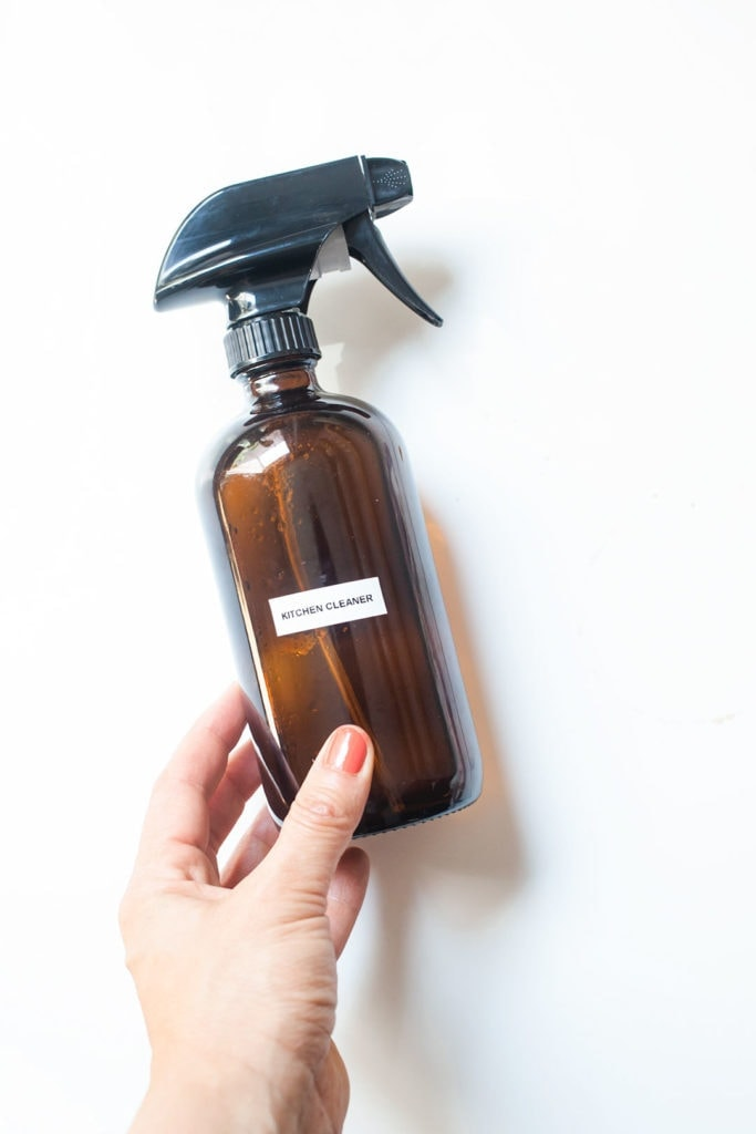 A spray bottle of non-toxic kitchen cleaner being held by a hand.