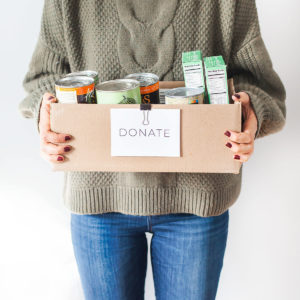 Woman in green sweater holding a donation box filled with food items.