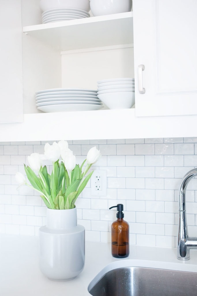 A vase of flowers by a sink with a kitchen cabinet open revealing white plates and bowls.