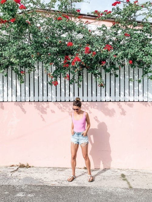 Ally Milligan in front of a pink wall with flowers in Harbour Island, the Bahamas.