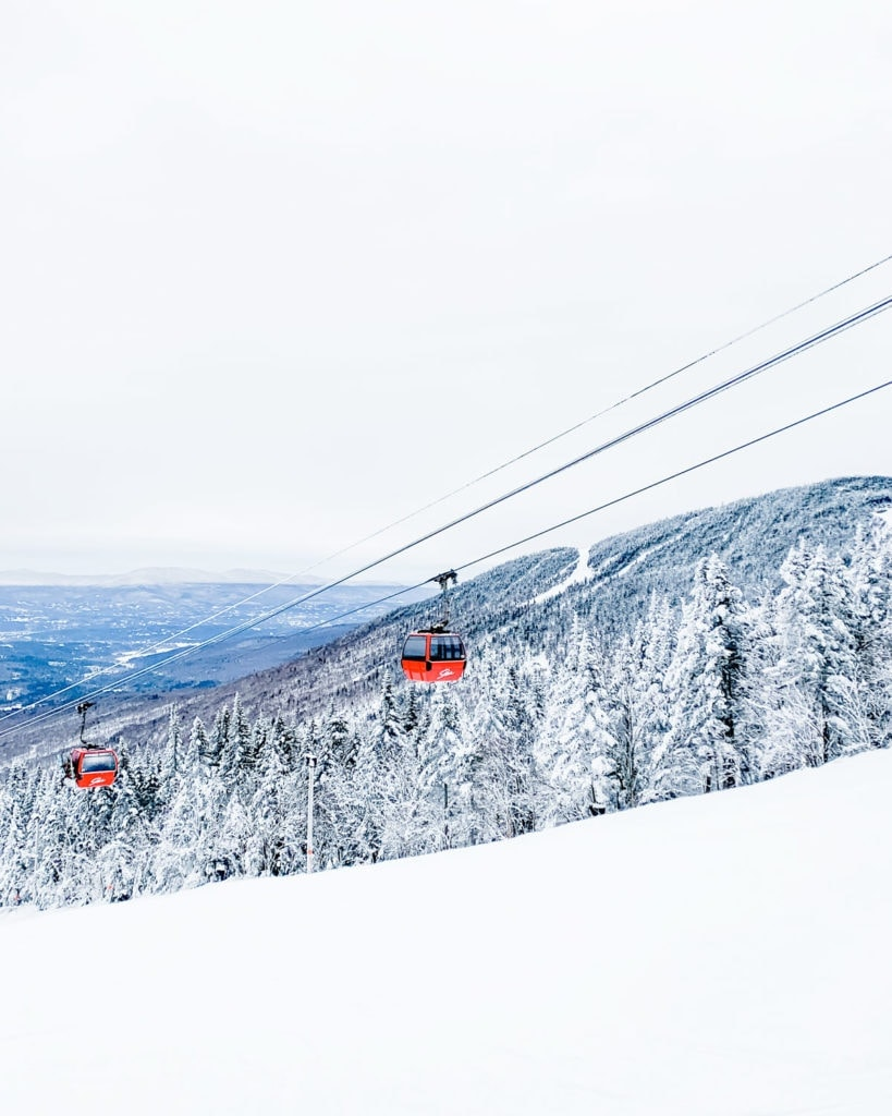 Red gondola in snowy scene at Stowe Mountain in Vermont.