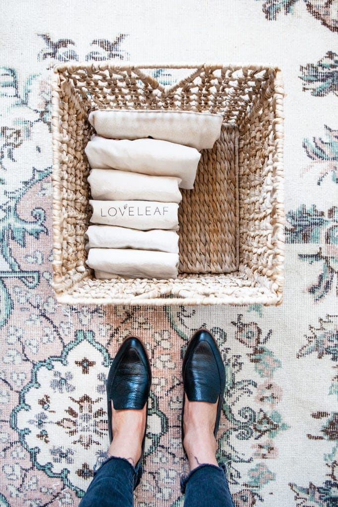 A woman's feet in loafers standing over a straw basket filled with canvas reusable grocery bags.