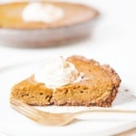 Gluten-free, dairy-free pumpkin pie slice on a white plate with a dollop of coconut whipped cream.