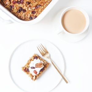 Pumpkin baked oatmeal with coconut whipped cream on a white plate.